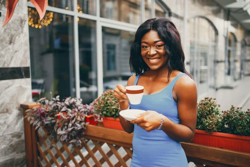 Black woman drinking coffee in a cafe