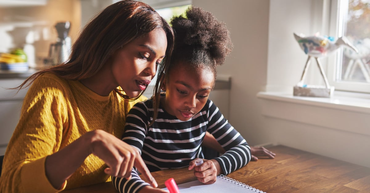 black mother teaching her daughter to read