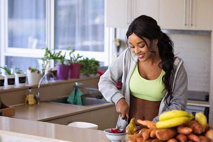 fit black woman slicing fruits