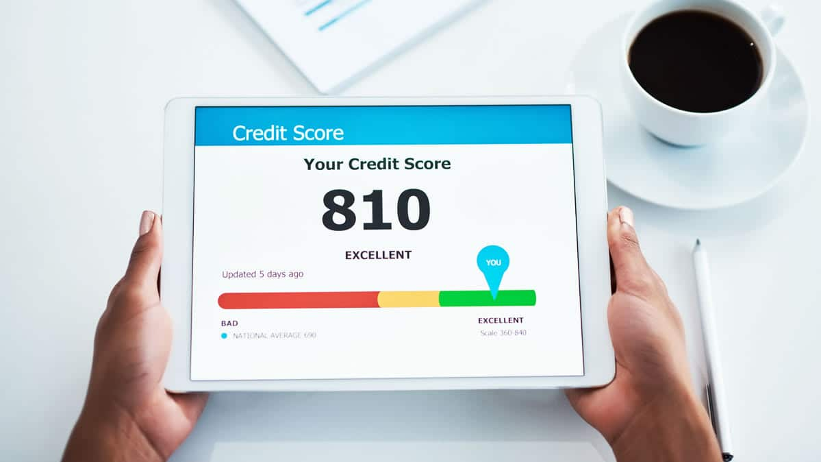 person holding a tablet and reading credit score report