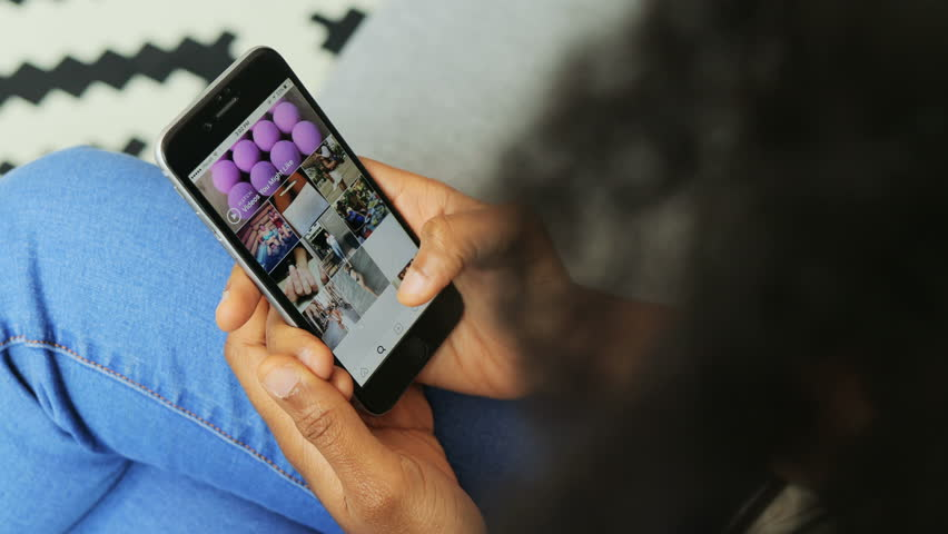 African American woman searching Instagram app on phone